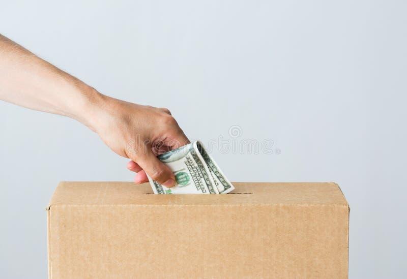 Sirva poner el dinero del dólar en la caja de la donación imagen de archivo