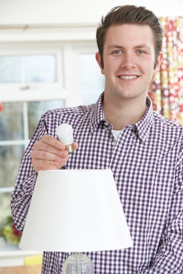 Sirva poner la bombilla de la energía baja LED en la lámpara en casa imagen de archivo libre de regalías