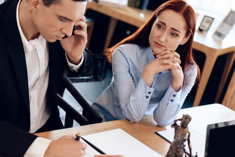 Sirva quién se divorcia a su esposa consulta sobre el teléfono con el abogado La mujer descompuesta se sienta al lado del hombre  imagen de archivo