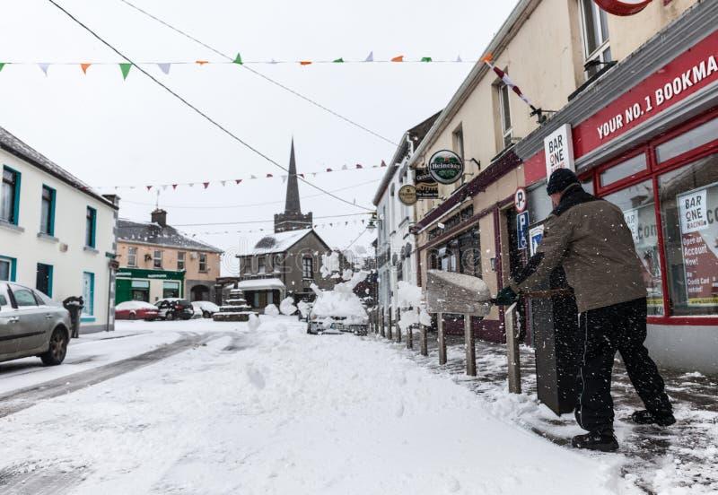Sirva raspar una nieve en el frente del pub imagen de archivo libre de regalías