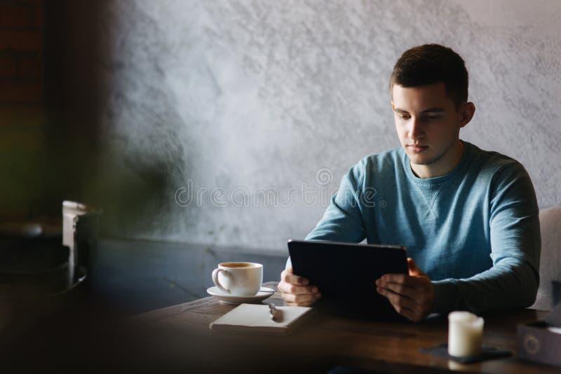 Sirva se está sentando en un café y utiliza una tableta imagen de archivo