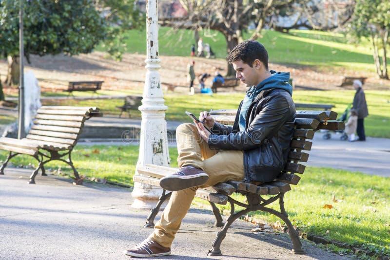 Sirva sentar y usar la tableta en el parque. fotos de archivo libres de regalías
