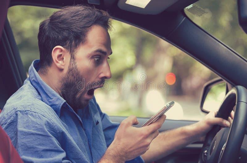 Sirva sentarse dentro del coche con el teléfono móvil que manda un SMS mientras que conduce imagen de archivo libre de regalías