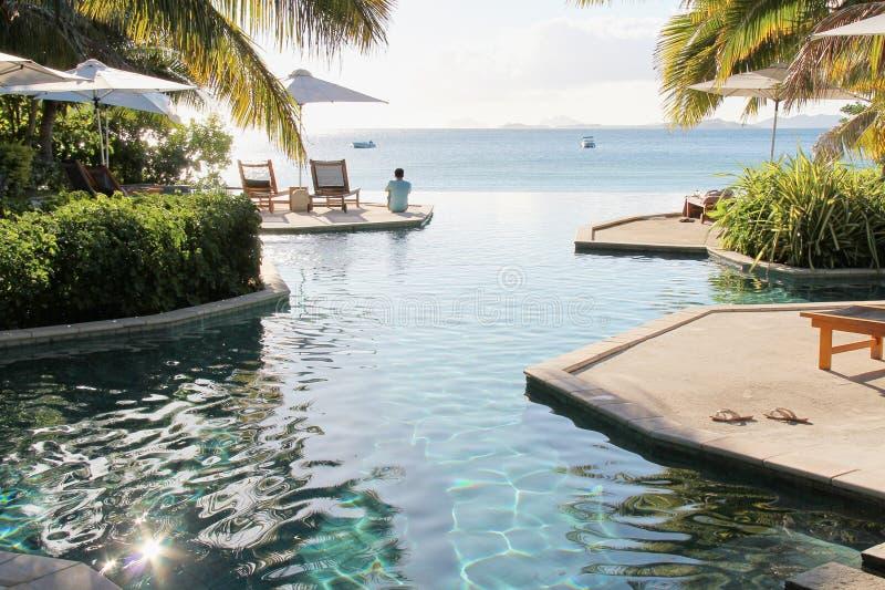 Sirva sentarse en el borde de la piscina del infinito foto de archivo libre de regalías
