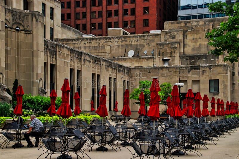Sirva sentarse en el patio de Chicago por completo de tablas con los paraguas rojos, mientras que trabaja en el dispositivo elect imágenes de archivo libres de regalías