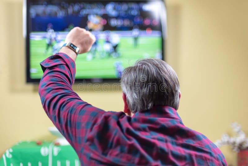 Sirva sentarse en el sofá que anima en el juego en la TV fotografía de archivo libre de regalías