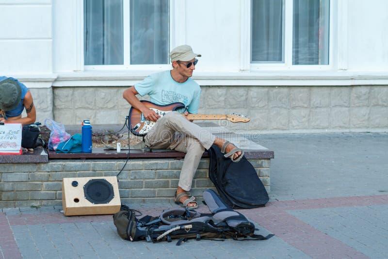 Sirva sentarse en la costa y jugar guitarra Crimea el pasamontañas 2018 el 15 de junio foto de archivo