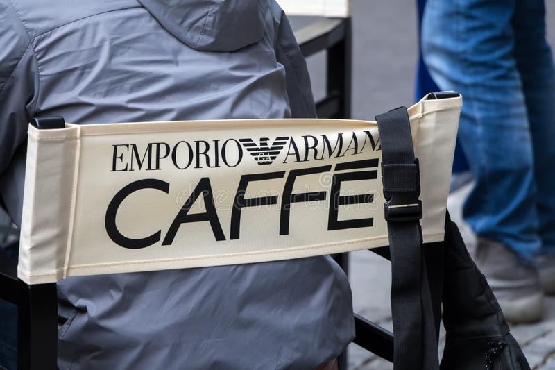Sirva sentarse en silla de Emporio Armani Caffe fotografía de archivo libre de regalías