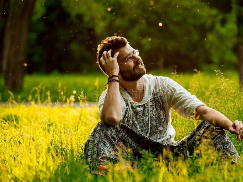 Sirva sentarse en una hierba en el parque, sonrisa soñadora fotografía de archivo libre de regalías