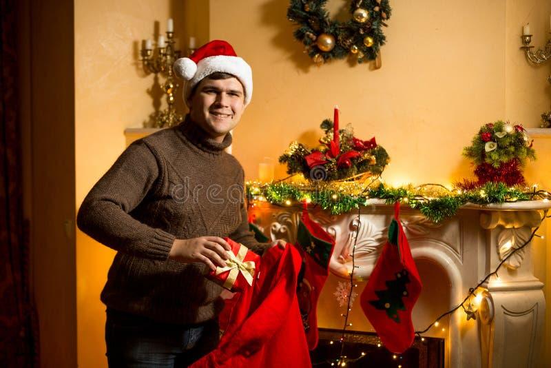 Sirva sostener el bolso rojo de Papá Noel con los presentes en la chimenea imágenes de archivo libres de regalías