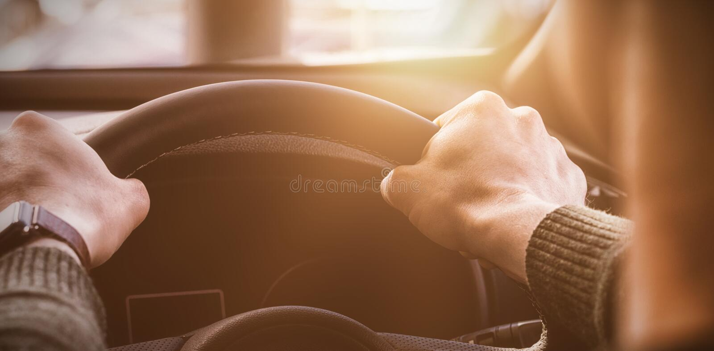 sirva sostener el volante de su coche fotografía de archivo