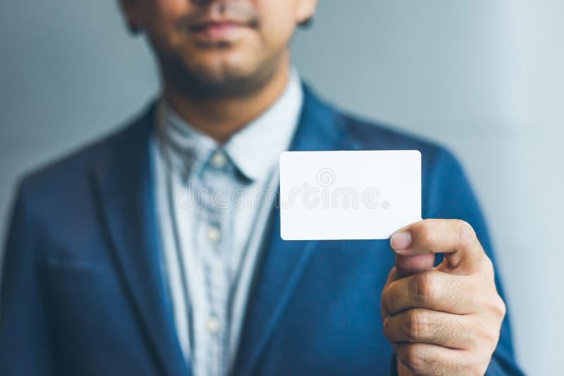 Sirva sostener la tarjeta de visita blanca, hombre que lleva la camisa azul y que muestra la tarjeta de visita blanca en blanco F imagen de archivo