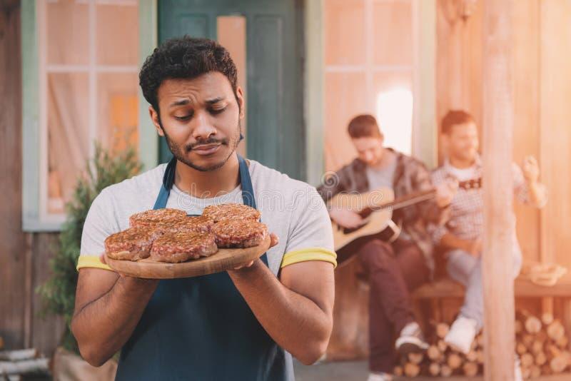 Sirva sostener las hamburguesas en el tablero de madera, amigos con la guitarra que se sienta detrás fotos de archivo