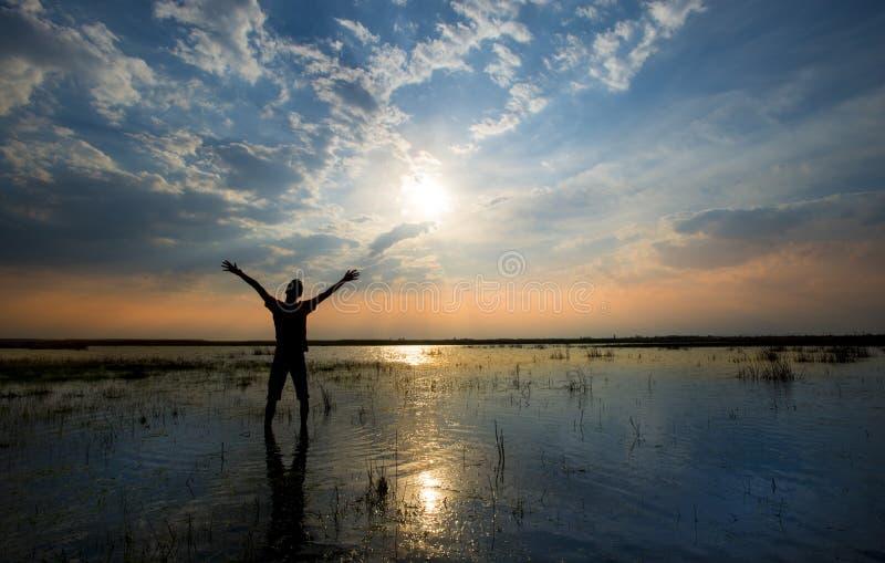 Sirva sostener los brazos para arriba en alabanza en puesta del sol mientras que estando en agua fotos de archivo libres de regalías