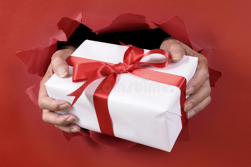 Sirva sostener o el donante de un regalo de la Navidad blanca con la cinta roja a través de un fondo de papel rasgado rojo fotografía de archivo