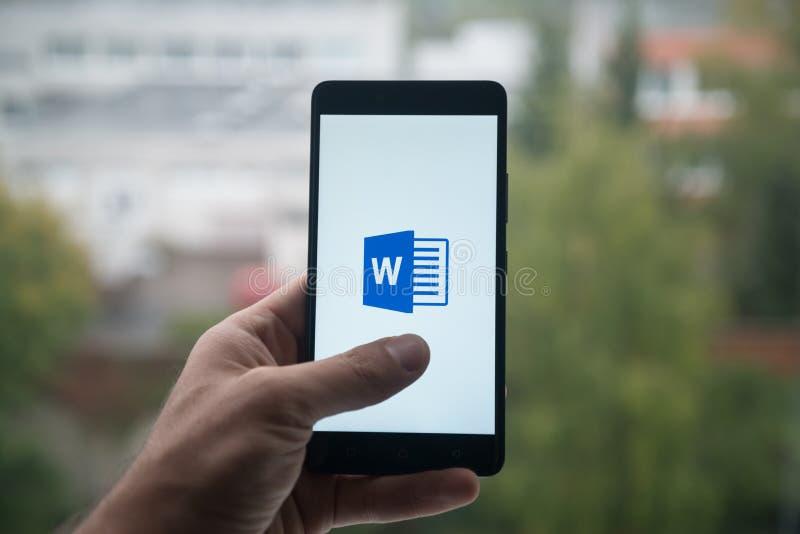 Sirva sostener smartphone con el logotipo del mensajero de la palabra del Microsoft Office con el finger en la pantalla fotografía de archivo