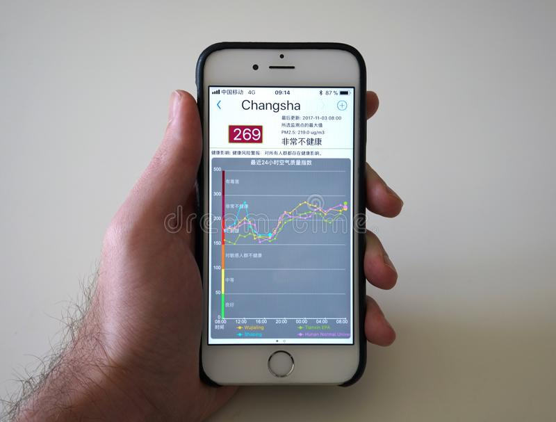 Sirva sostener smartphone con los apps del índice de la calidad del aire de AQI que muestran el pico púrpura de la contaminación  foto de archivo