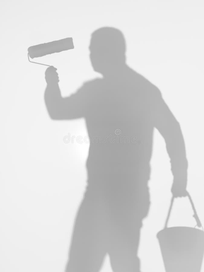Sirva sostener un rodillo de pintura y un cubo, silueta foto de archivo libre de regalías