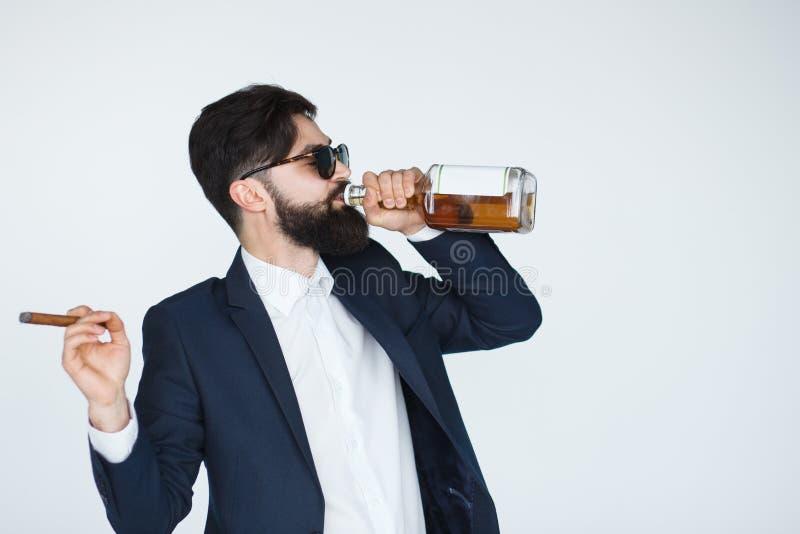 Sirva sostener un whisky y la consumición de la botella fotos de archivo libres de regalías