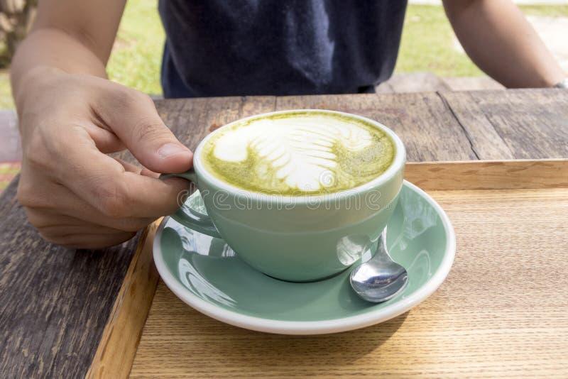 Sirva sostener una taza de latte caliente del té verde imágenes de archivo libres de regalías