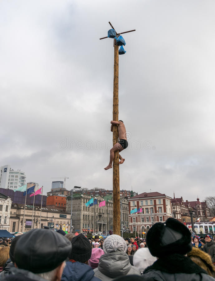 Sirva subir el polo para el premio durante el carnaval Maslenitsa del invierno imagenes de archivo