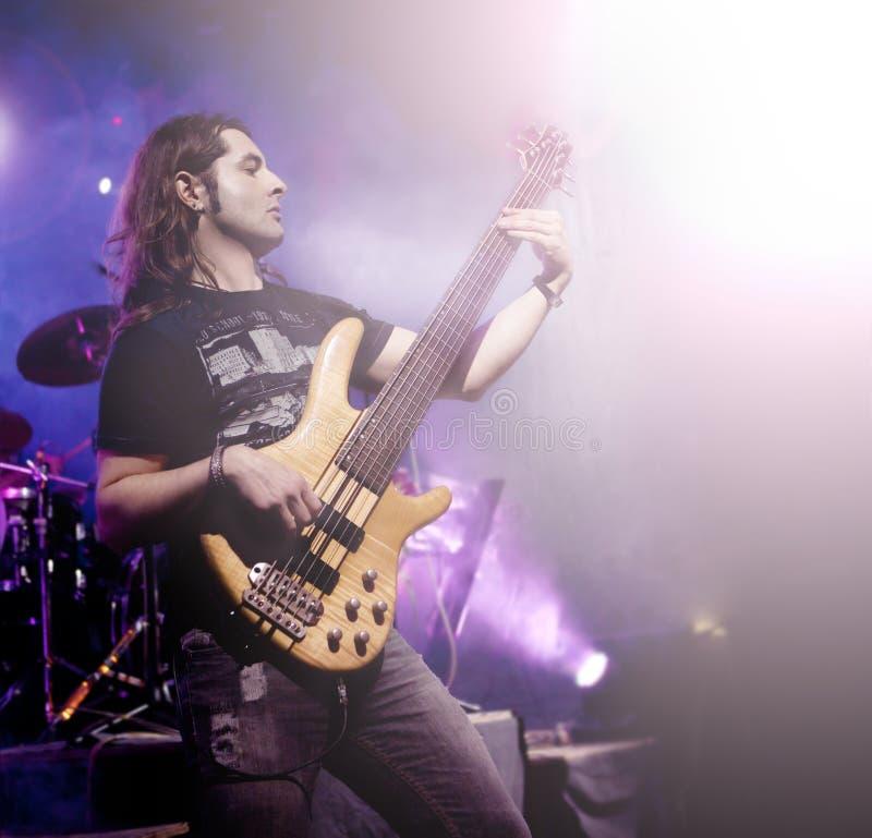 Sirva tocar la guitarra baja en secuencia viva del concierto Fondo de la música en directo foto de archivo libre de regalías
