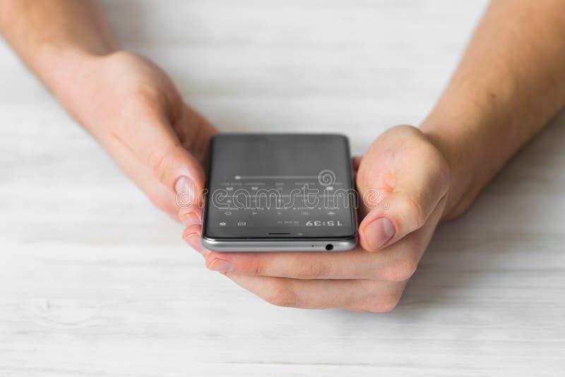 Sirva usando smartphone negro un teléfono elegante de la pantalla táctil en manos del café cerca para arriba, vintage colorea imagen de archivo