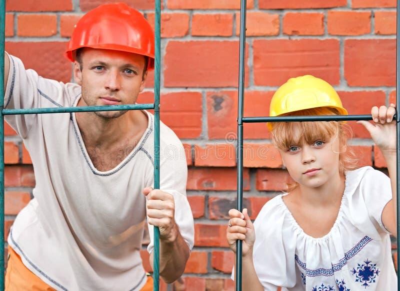 Sirva y su hija como trabajadores de una construcción fotografía de archivo