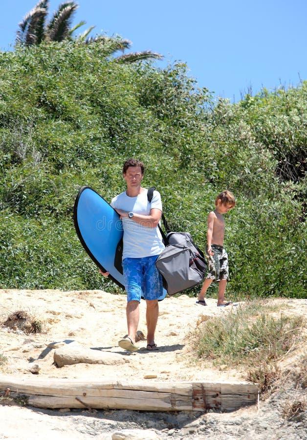 Sirva y su hijo que llega la playa para practicar surf imágenes de archivo libres de regalías