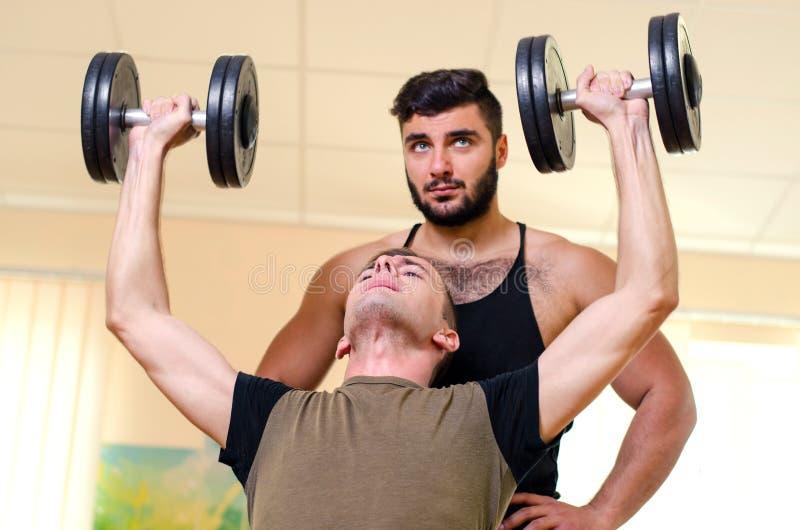 Sirva y su instructor personal que ejercita con pesas de gimnasia en el gimnasio Ejercicios de la técnica para los hombros atleta foto de archivo libre de regalías
