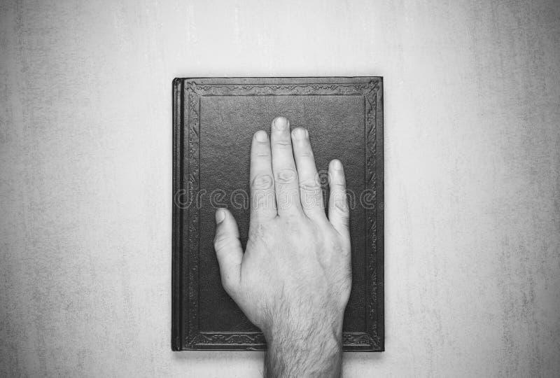 Sirve la mano en el libro, el juramento en la biblia Primer de la visión superior foto de archivo libre de regalías