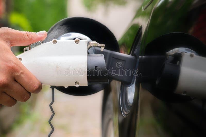 Sirve la mano que inserta el enchufe del cargador en el coche eléctrico en fondo verde del ambiente El nuevo vehículo de la energ imagenes de archivo