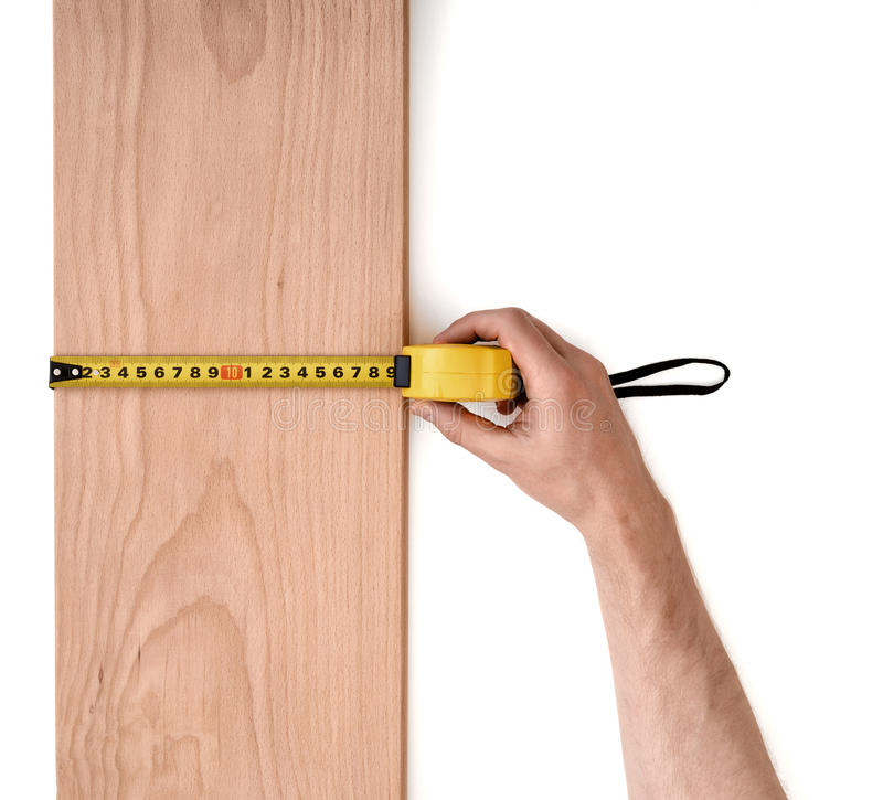 Sirve la mano que mide el tablón de madera con una línea de la cinta aislada en el fondo blanco fotografía de archivo