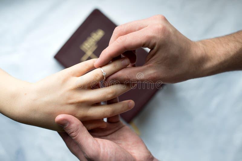 Oferta de las manos de los anillos de compromiso imagen de archivo