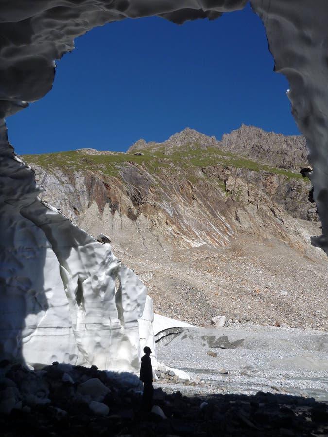 Sirve la silueta en la entrada de una cueva del glaciar foto de archivo libre de regalías