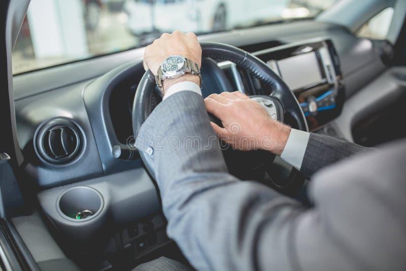 Sirve las manos en el volante del nuevo electro coche imagen de archivo libre de regalías