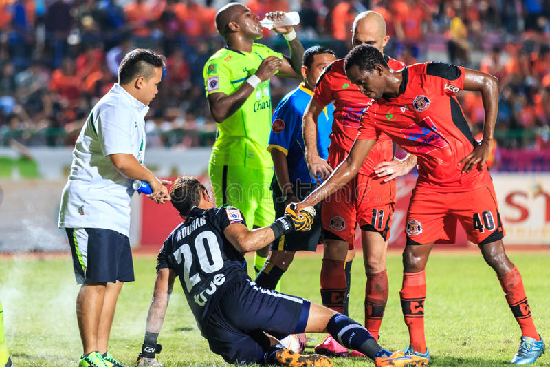 SISAKET THAILAND-SEPTEMBER 12: Adefolarin Durosinmi of Sisaket F. C. (orange) show good sportsmanship during Thai Premier League match between Sisaket FC and stock photo