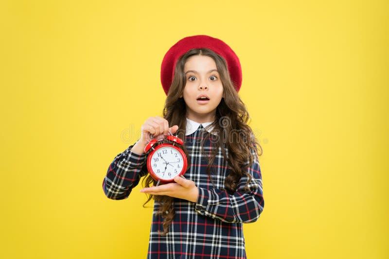 Sista chansenstopptid Det angelägna barnet oroade om stopptid på gul bakgrund Stressad liten flickainnehavklocka fotografering för bildbyråer