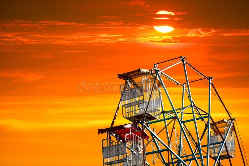 sista ljus av solnedgången på himmel och konturferrishjulet royaltyfri foto