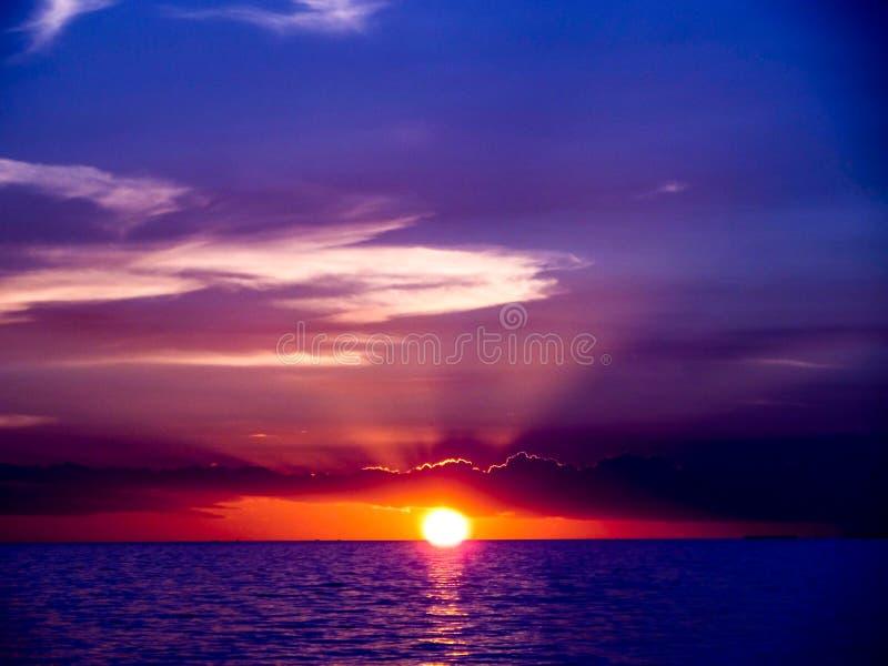 sista ljus solnedgång på mörkret - blått hav och grå blå himmel arkivfoton