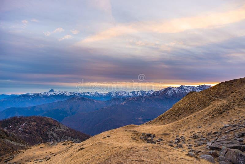 Sista varmt solljus på den alpina dalen med glödande bergmaxima och sceniska moln Italienska franska fjällängar, sommarloppdestin royaltyfri bild