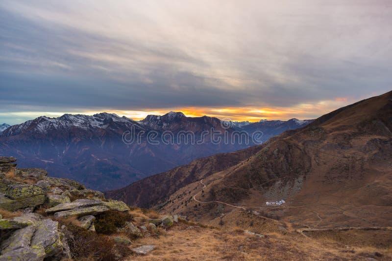 Sista varmt solljus på den alpina dalen med glödande bergmaxima och sceniska moln Italienska franska fjällängar, sommarloppdestin arkivfoto
