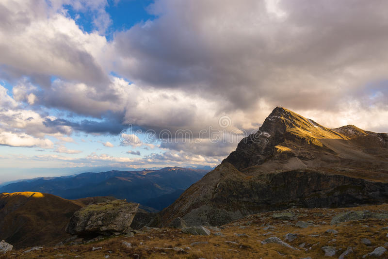 Sista varmt solljus på den alpina dalen med glödande bergmaxima och sceniska moln Italienska franska fjällängar, sommarloppdestin royaltyfria bilder