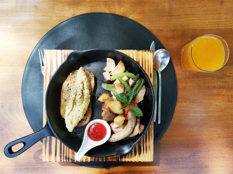 Sistema americano del desayuno, tortilla, salchicha, tocino, tomate fresco y verdura en placa negra con la bifurcación de la cuch imagen de archivo libre de regalías