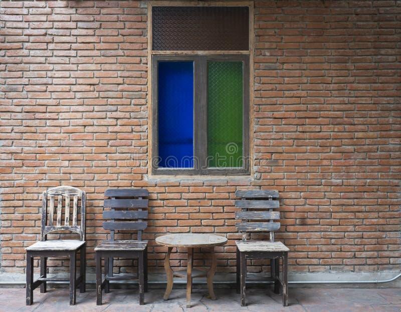 Sistema antiguo de sillas y de la tabla de madera con la ventana antigua en la pared de ladrillo vieja fotografía de archivo libre de regalías