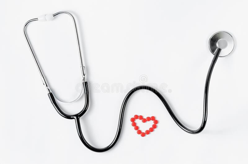 Sistema cardiovascular Estetoscópio e pílulas vermelhas em forma de coração sobre fundo branco Copiar espaço fotos de stock