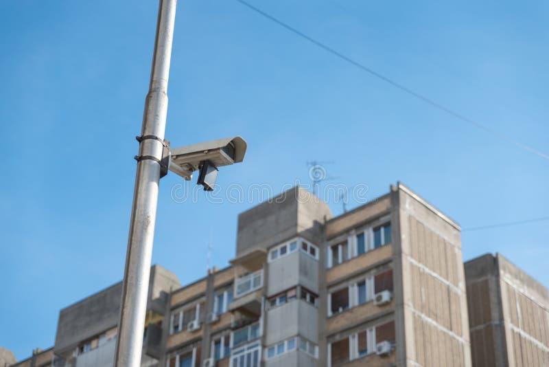 Sistema da câmara de vigilância da segurança do cctv da cidade unido no polo de sinal com fundo claro do céu azul imagem de stock