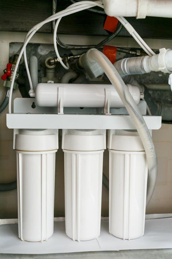 Sistema da purificação de água da osmose reversa em casa A instalação de filtros da purificação de água sob a banca da cozinha no fotos de stock royalty free