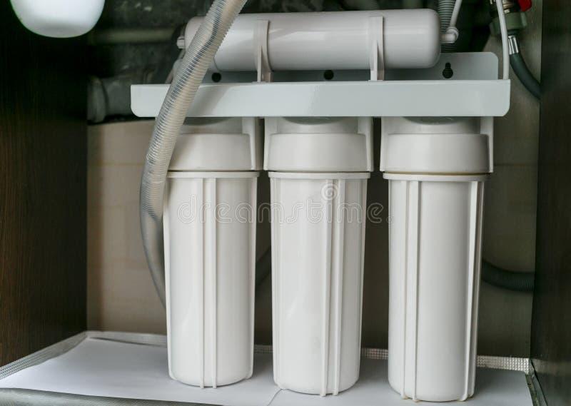Sistema da purificação de água da osmose reversa em casa A instalação de filtros da purificação de água sob a banca da cozinha no fotografia de stock royalty free