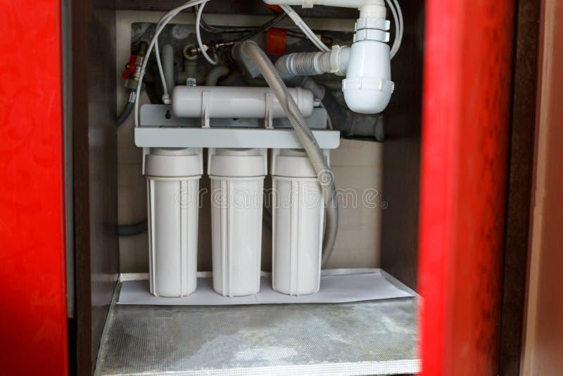 Sistema da purificação de água da osmose reversa em casa A instalação de filtros da purificação de água sob a banca da cozinha no imagens de stock